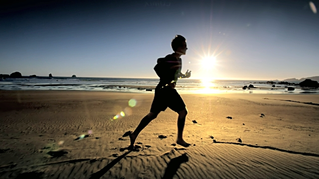A boy running on a beach after making it onto the shores of the land of opportunity.