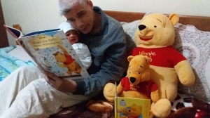 Author Rico Lamoureux and son Journey Teller reading Winnie the Pooh with stuffed Poohs.