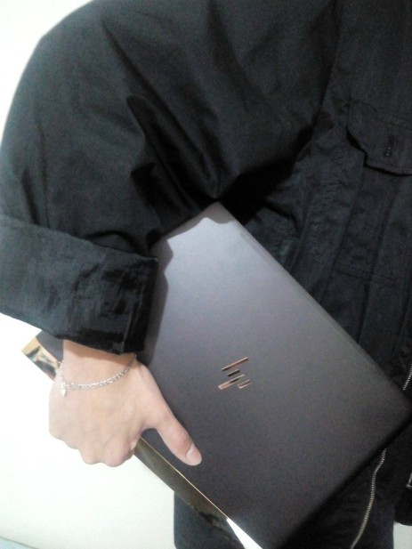 Hand holding hp Spectre, on the go.