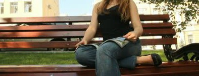 Girl sitting on park bench reading magazine, for music video script by The Flash Fiction Ponder.