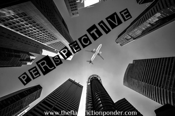 Tops of skyscrapers, bottom of airplane, image for 'Perspective' by The Flash Fiction Ponder.
